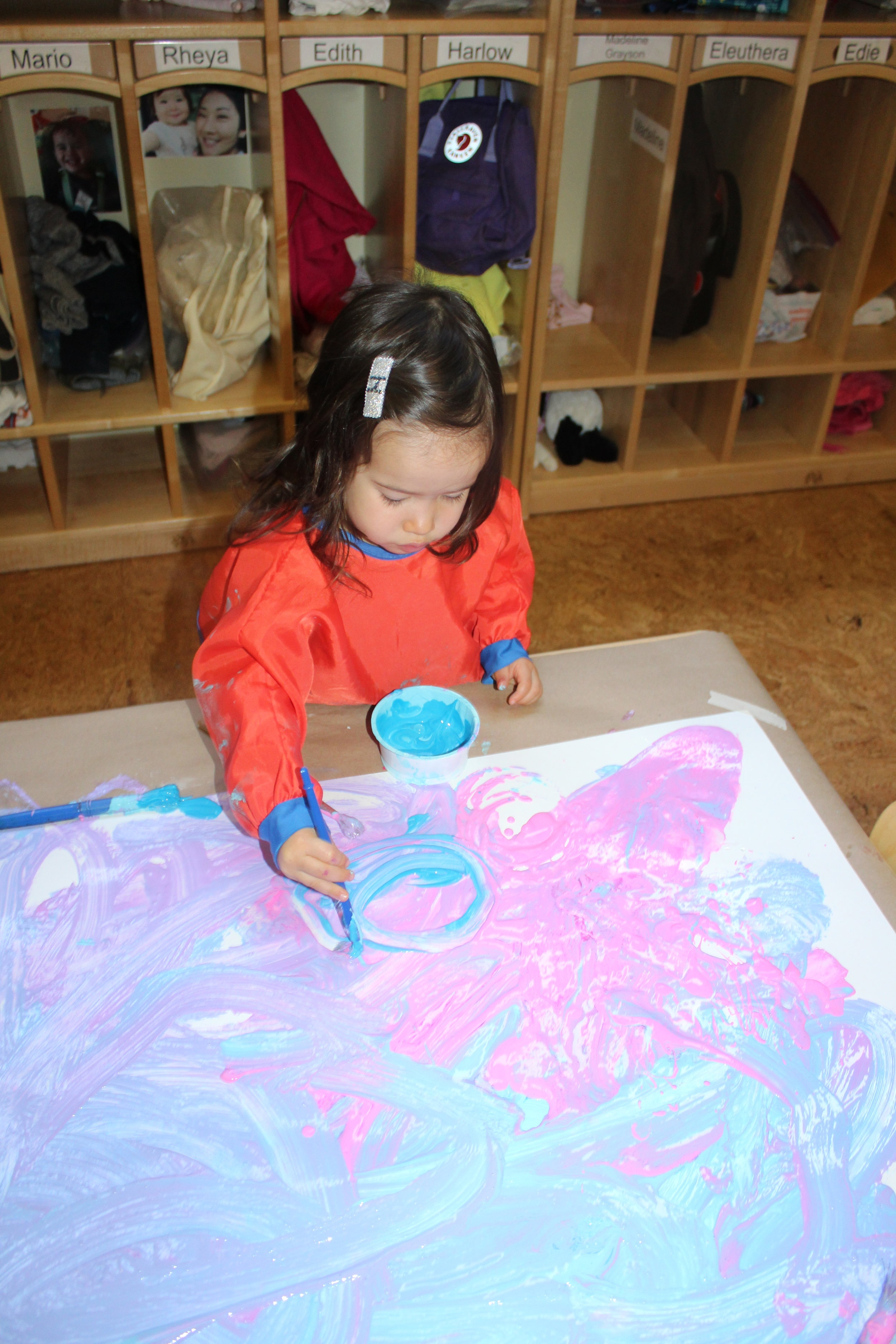 """Painting provides texture and color exploration. It enables children to create and become curious as they paint. Combining colors and using a paintbrush or their hands to explore are elements that help them create and discover. As Ellie was mixing the colors and maneuvering the paintbrush, she articulated, """"The moon!"""" Harlow was making circular movements, """"Look Sandra, circles!"""" Painting allows them to express themselves and develop their creativity freely.  Painting with young children not only helps their creative development but it also stimulates their brain. Stimulating children's brain can also improve other areas of their development; for example, developing their fine pincer grip or learning about color mixing."""