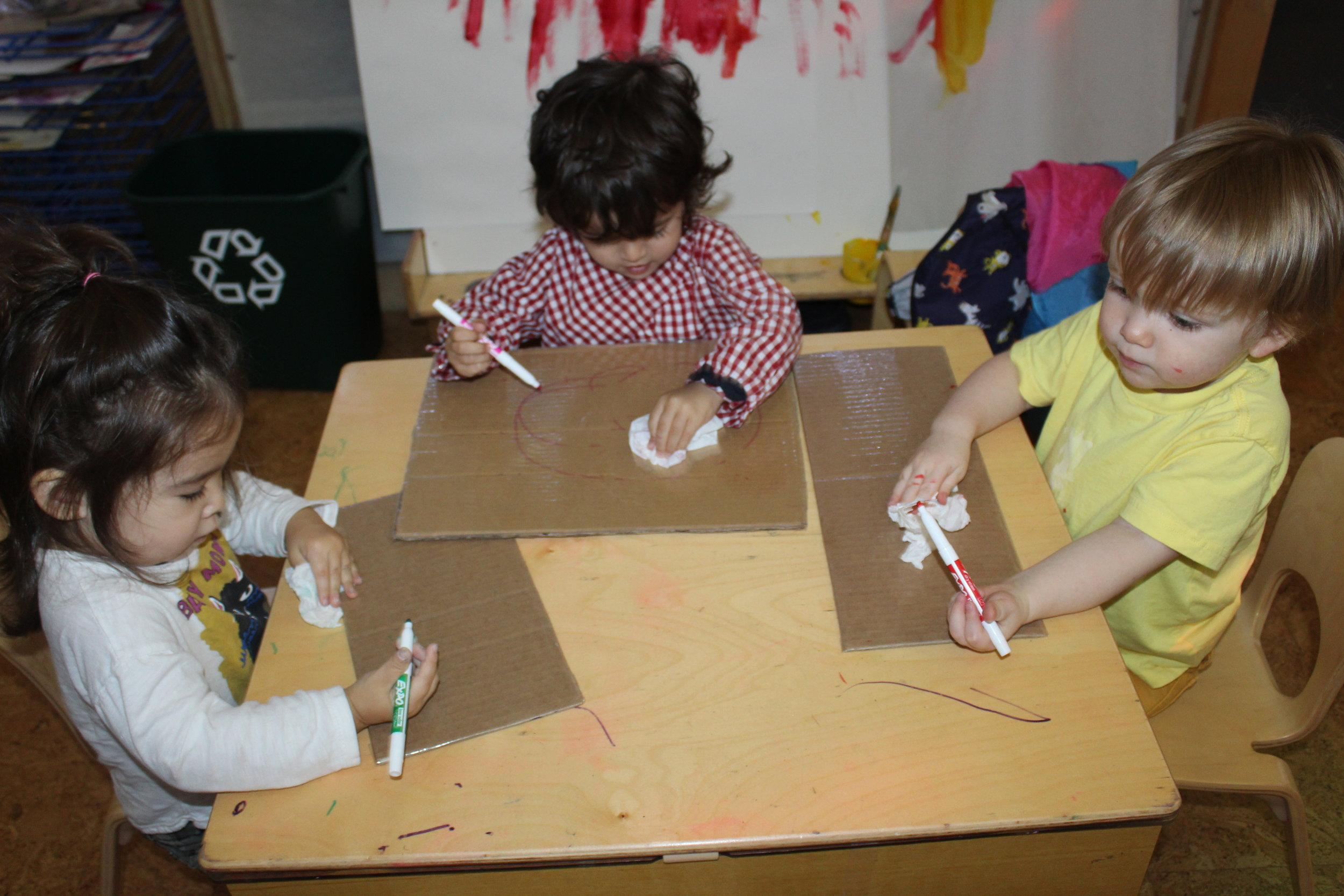 The children are drawing on a particular contact paper in which they can use erasable markers. They draw zig-zag, straight, or curvy lines, or pictures that represent something.