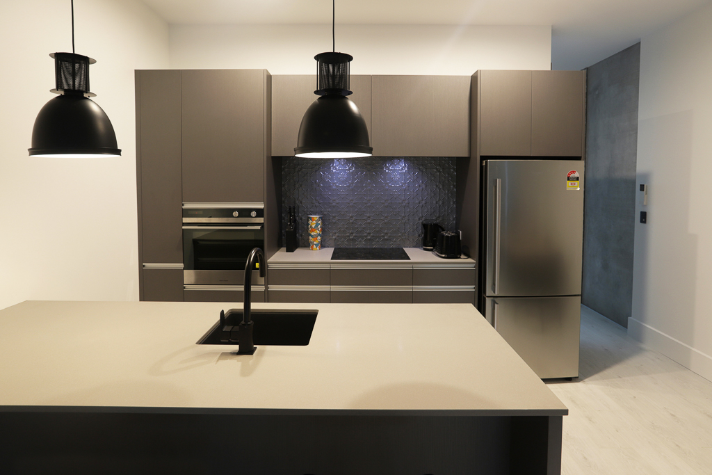 Patterned pressed alloy splashback and engineered stone benchtop