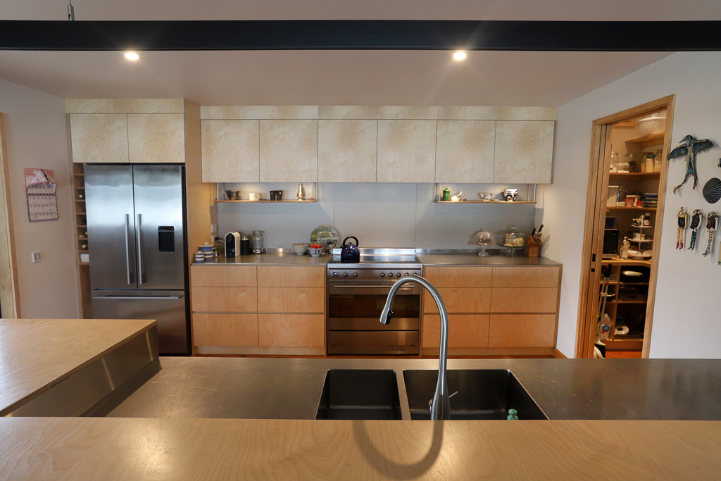 Contemporary kitchen with oiled birch plywood and plate stainless benchtops