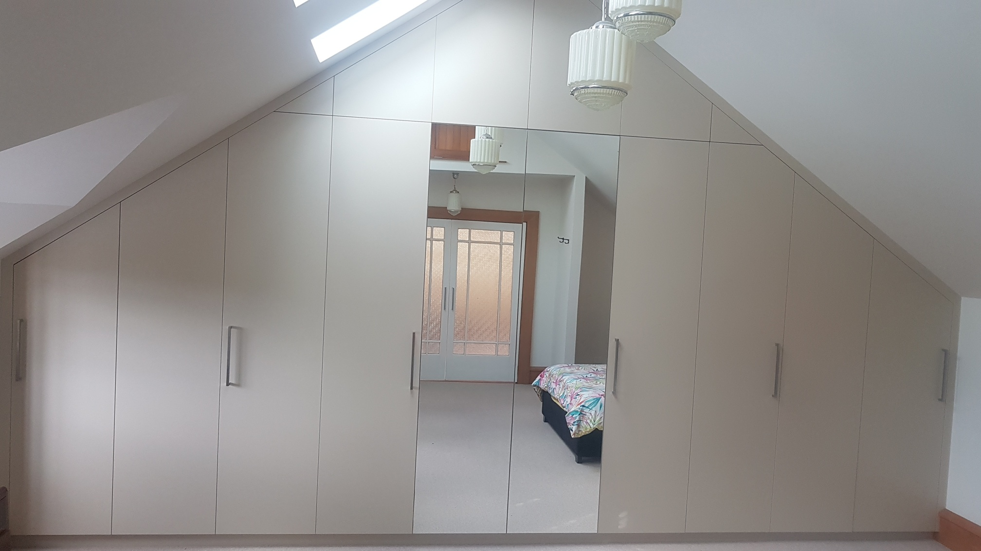 Large custom wardrobe in room with A-frame roof