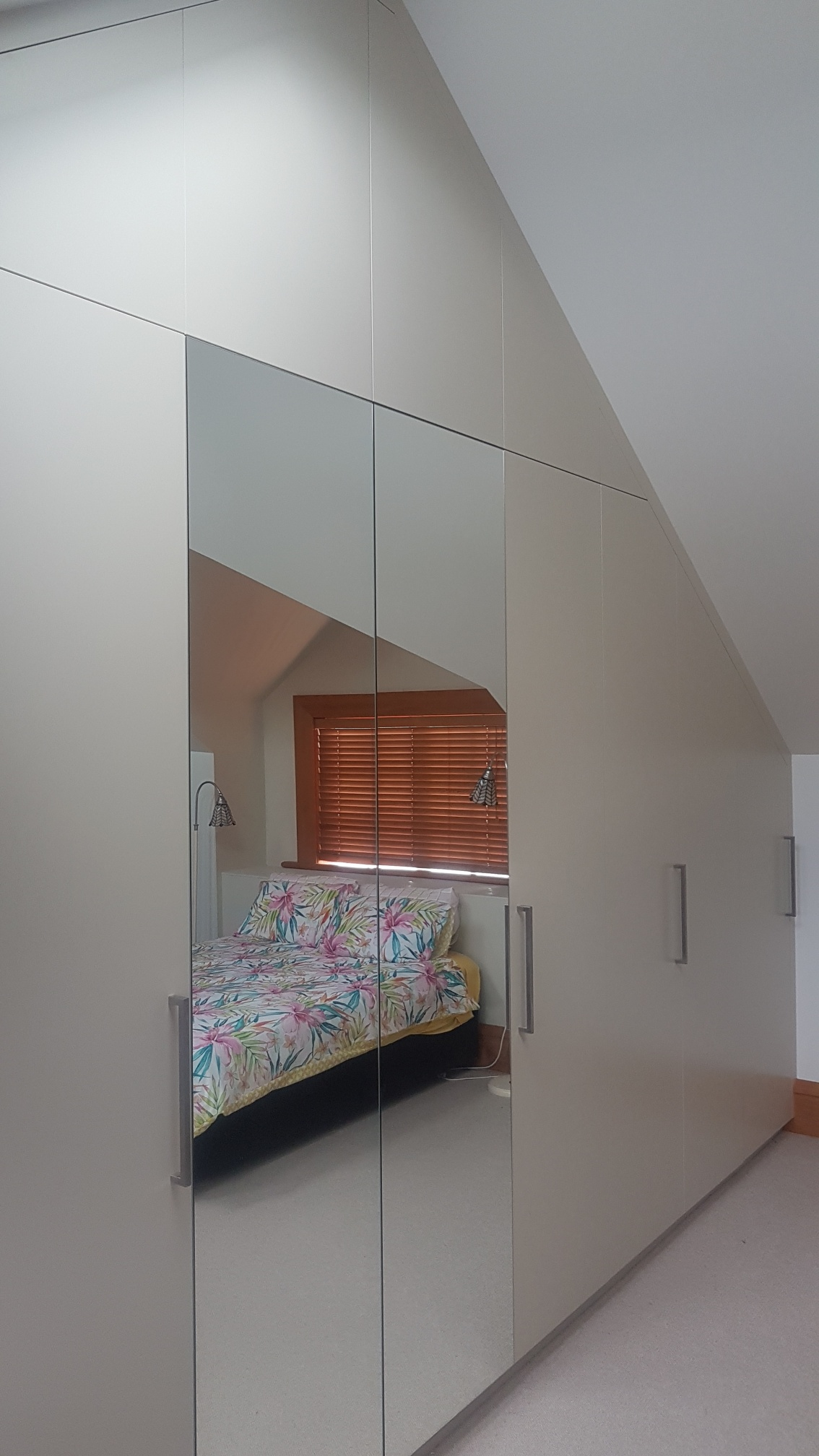Large custom wardrobe in bedroom with sloped roof