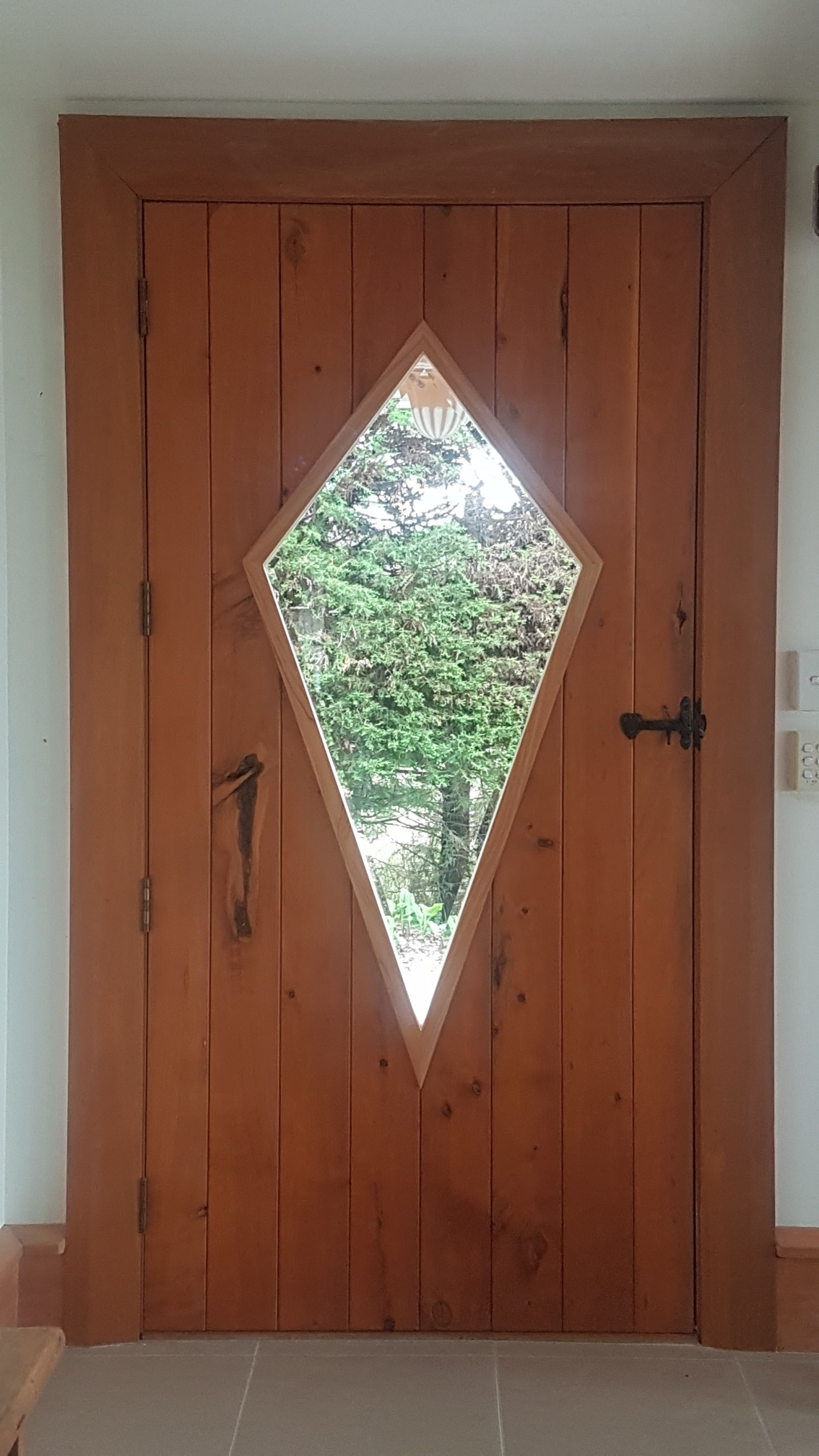 Macrocarpa door with diamond shaped cut out for extra light