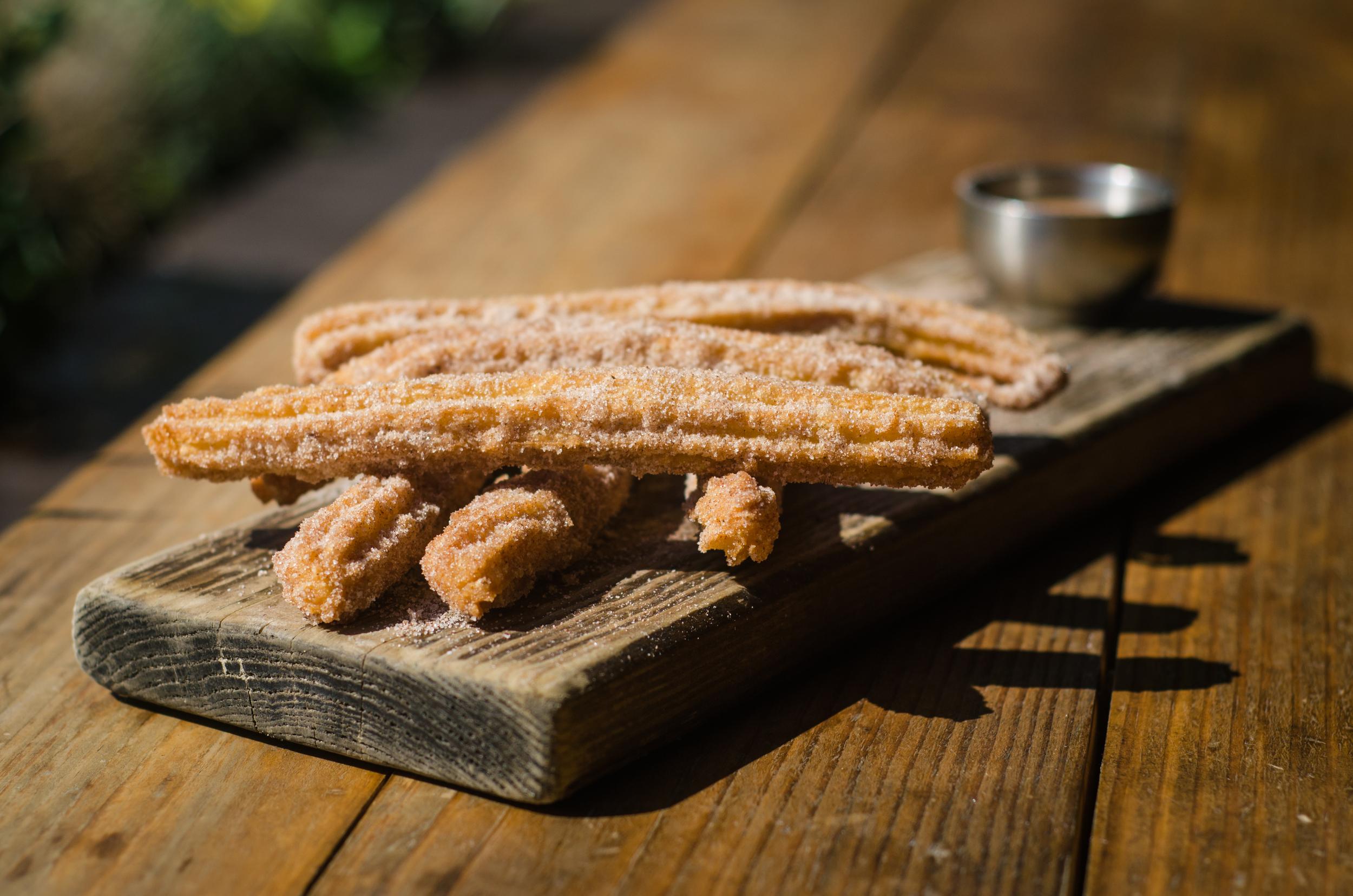 Saint Añejo 's churros with cinnamon sugar and dulche de leche sauce for dipping