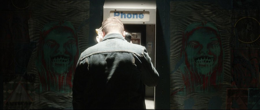Pictured: A passing shadow in the night. But what really makes it weird is the pay phone. When was the last tine you saw one of those?