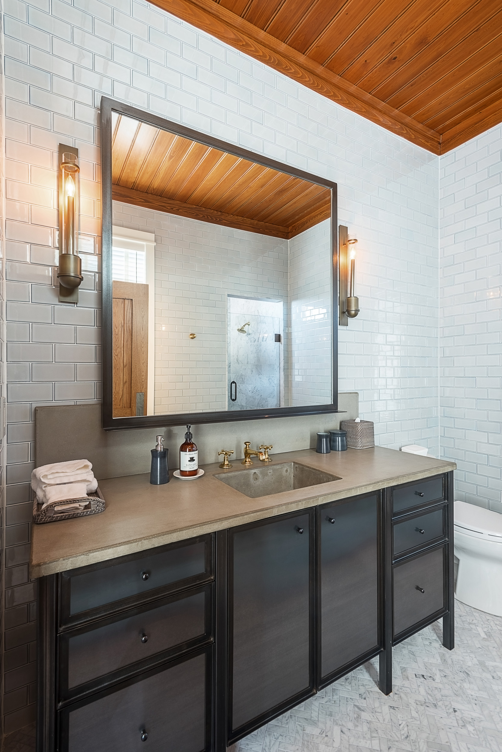 Interior photography of bathroom vanity, custom built with steel cabinetry fronts and concrete counter top.