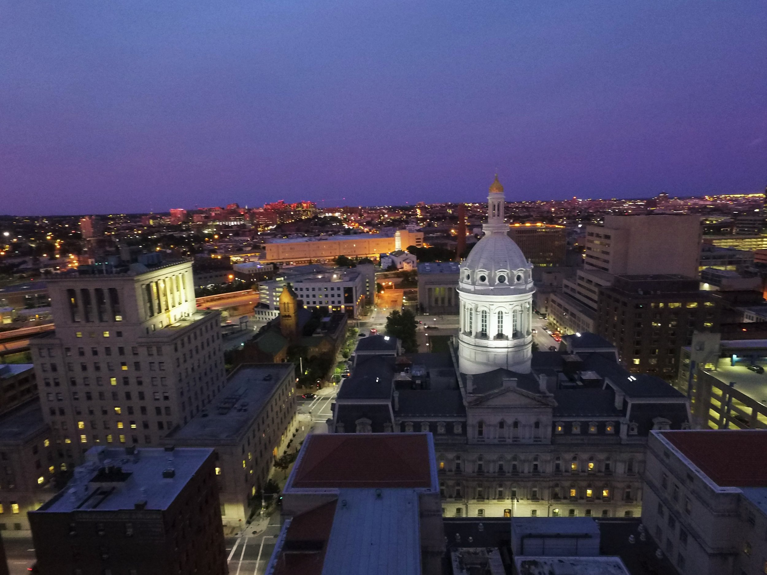 Still image of Baltimore City Hall from above. Shot by drone during dusk. Blue skies and city lights abound.