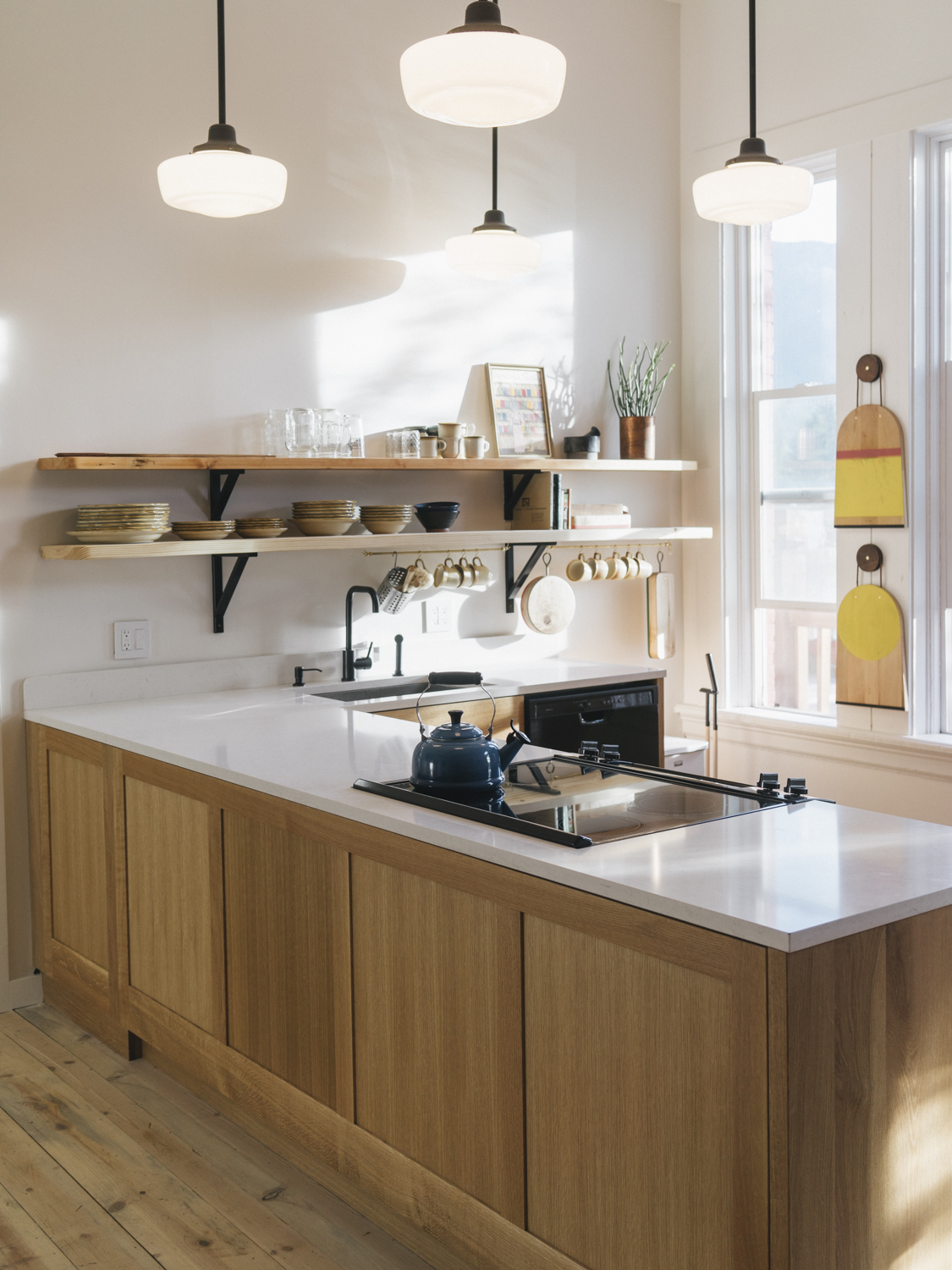 Custom Oak cabinets by  Phloem Studio  accented by beautiful  M.Crow  cutting boards in our communal kitchen