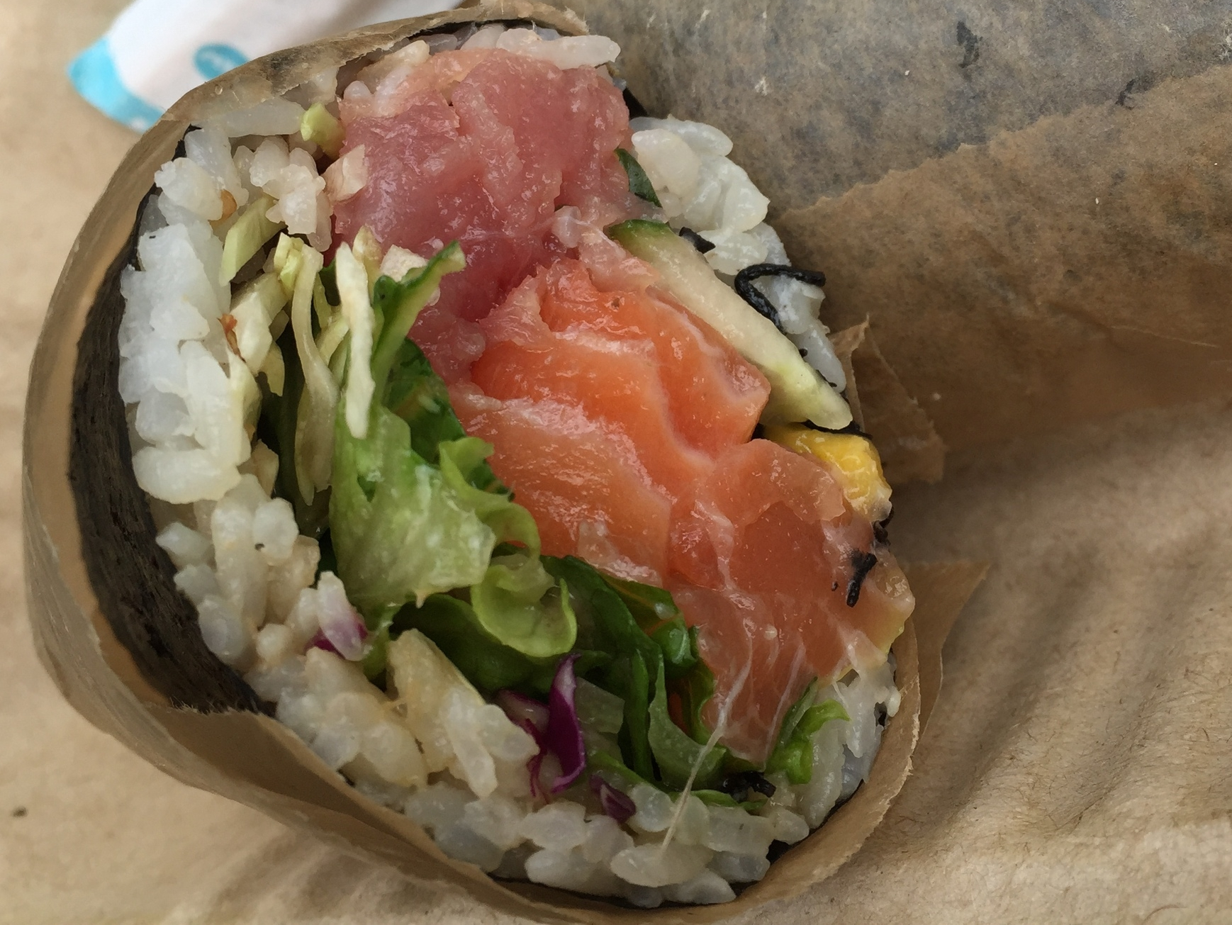 Here's a poke burrito found at Pokeworks in midtown New York. Be prepared when you go because the line for that place can get really long especially starting at the 11am lunch rush. This one is wrapped in seaweed paper with rice, a mix of vegetables and a mix of salmon and tuna sashimi.
