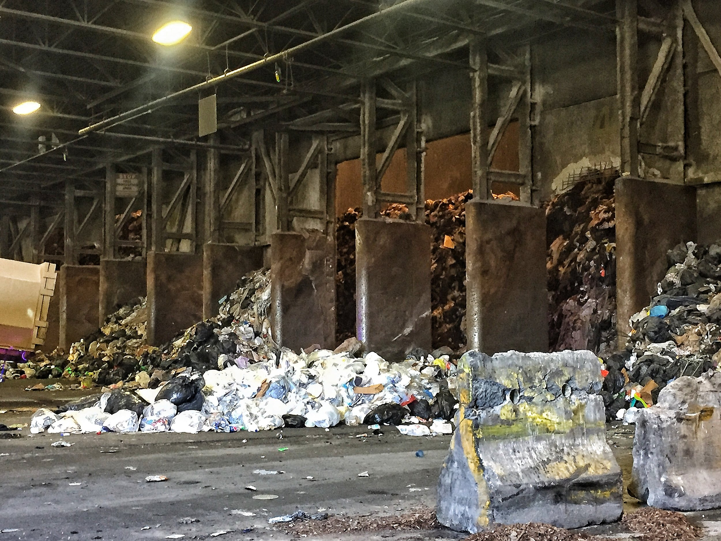 Trash is dumped by the trucks on to the floor. A bulldozer will spread the trash to see if there are any items that shouldn't be there such as large appliances or furniture. Then it is pushed to the trough below.