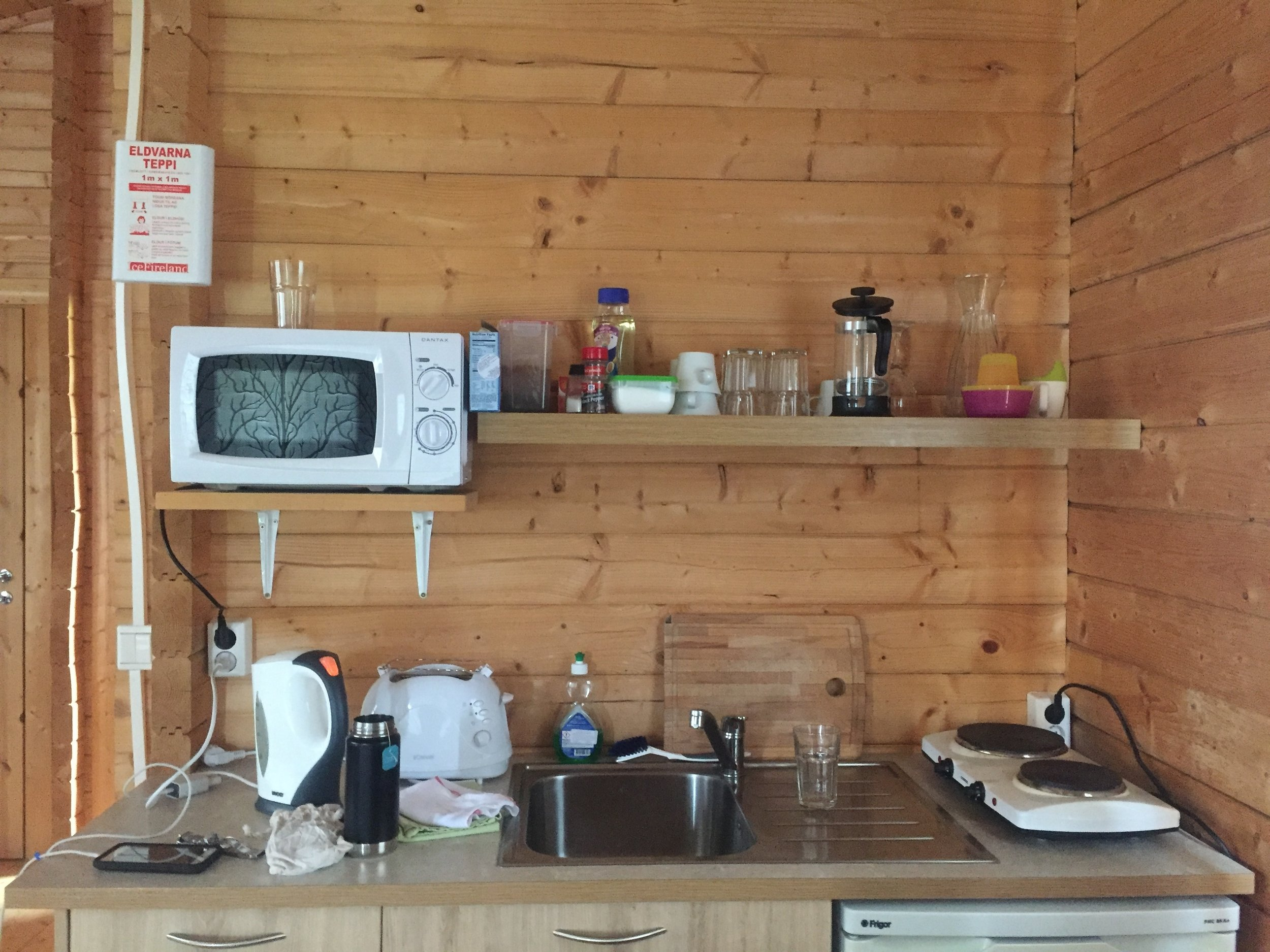 Small kitchen at Bragdavillir Cottages equipped with microwave, stove, hot water, French press and toaster.