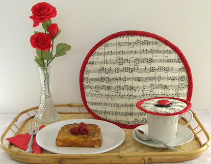 Thinsulate insulated  Music Tea Tabard on a teapot and a Music Krescendo Kup Kap on the cup &saucer.