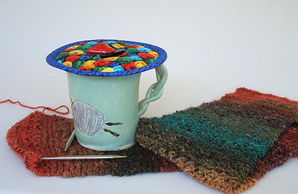 Thinsulate insulated Yarn Skeins Kup Kap on ceramic mug.