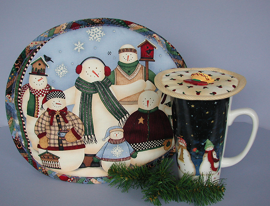 Thinsulate insulated Snowmen Family Reunion on a teapot.                Thinsulate insulated Rosebud Rhapsody Kup Kap on tall mug.