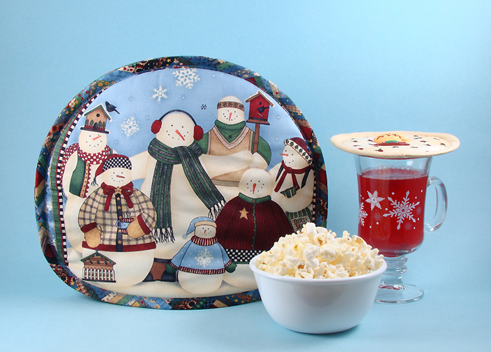 Thinsulate insulated Snowmen Family Reunion Tea Tabard on a teapot.                            Thinsulate insulated Rosebud Rhapsody Kup Kap on glass mug.