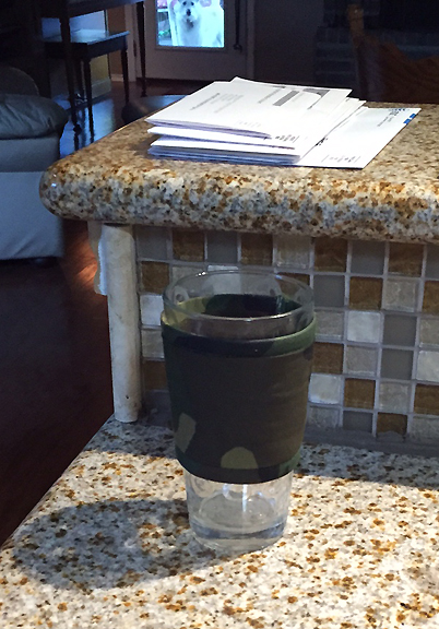 Thinsulate insulated Camouflage Kup Kollar on a 16 ounce drinking glass.