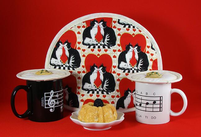 Thinsulate insulated Tuxedo Kats Tea Tabard on a teapot and Cream Elegance Kup Kpas on two musical mugs.