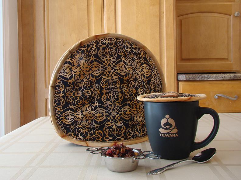 Insulated thinsulation Words of Friendship Tea Tabard over a teapot; Insulated thinsulation Friendship Kup Kap on Teavana large mug.