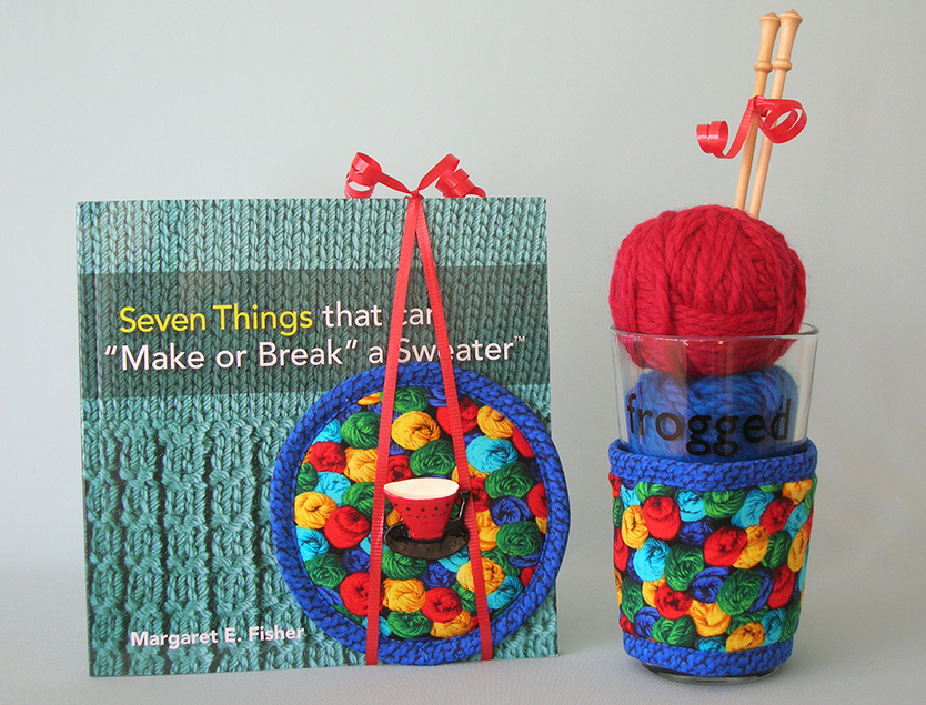 Thinsulate insulated Yarn Skeins Kup Kap tied to book and Yarns Kup Kollar on 16 ounce pint glass filled with yarn and knitting needles.