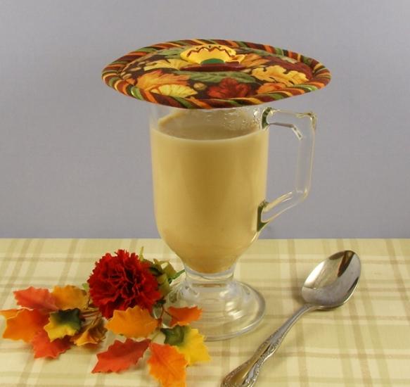 Thinsulate insulated Fall Leaves Kup Kap on a mug of hot pumpkin chai tea latte.