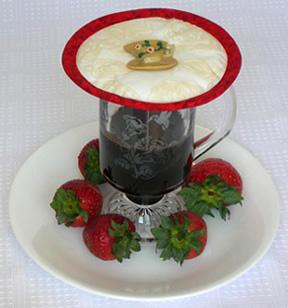 Thinsulate insulated Kup Kap lid on glass mug of hot melted chocolate.