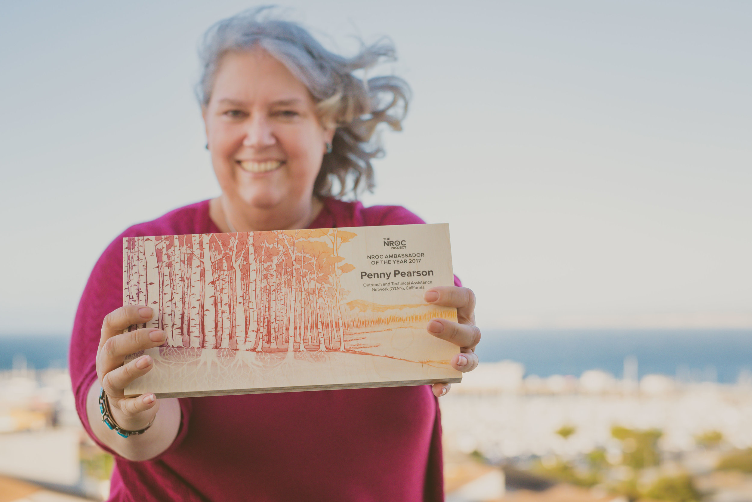 2017 Ambassador award winner and California Adult Education professional, Penny Pearson proudly displays her award featuring the Networked for Change aspen illustration.