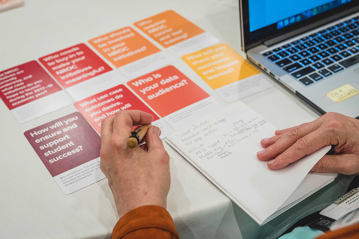 A conference participant plans future educational initiatives with assistance from card deck, notebook, and digital tools provided at the event.