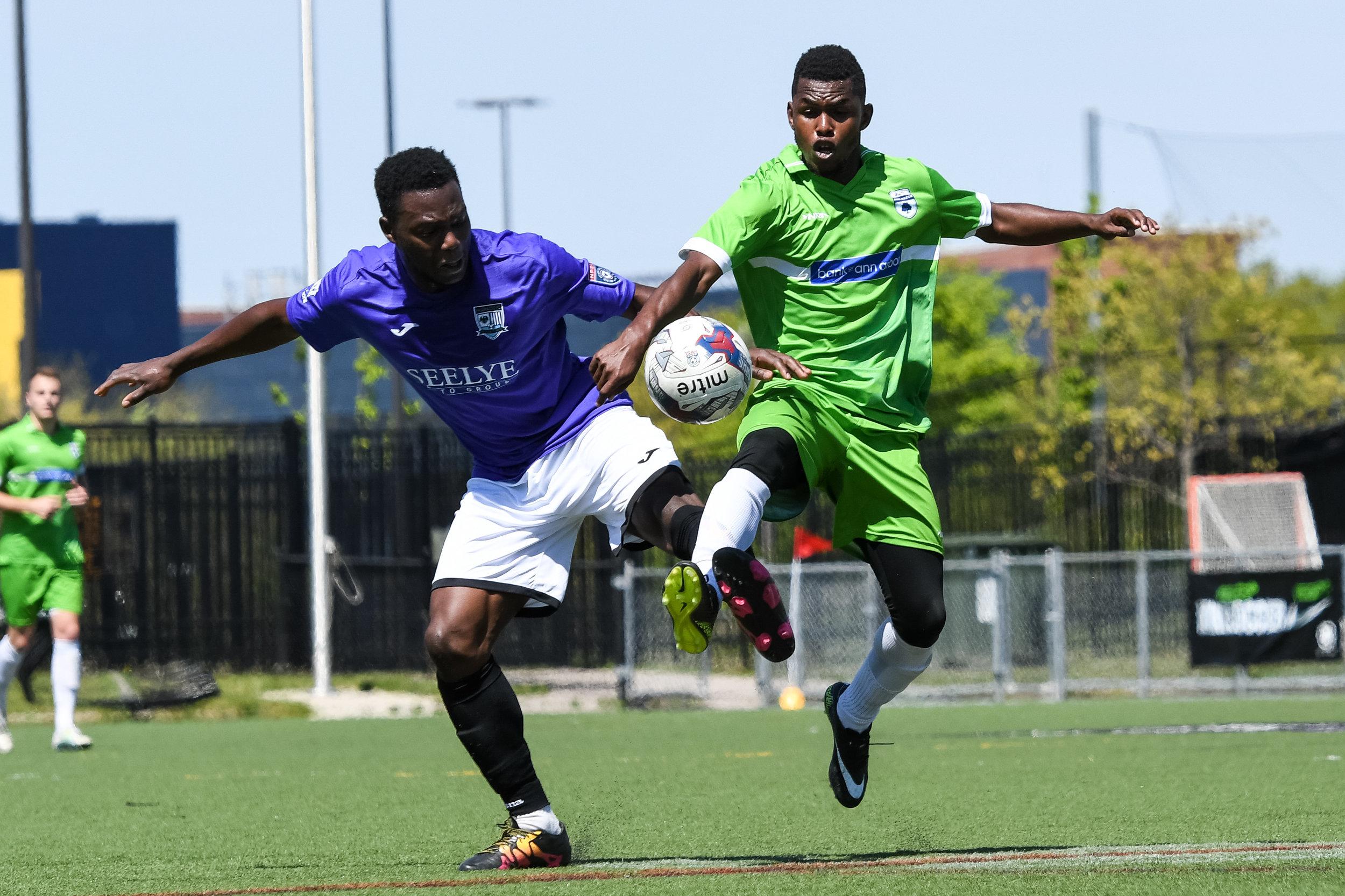 Jesse Muskwe looks to win the ball against Kalamazoo FC's Ade Adeniyi