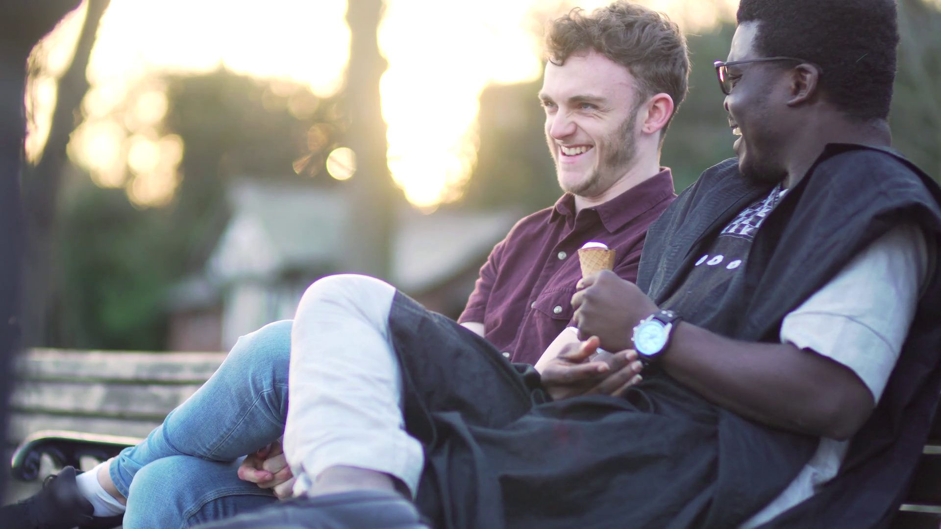 videoblocks-two-men-happy-gay-couple-pair-talking-and-eating-ice-cream-at-sunset-friends-sitting-laughing-and-smiling-young-handsome-males-multi-ethnic-diversity-white-caucasian-and-black-nature-trees-and-romantic-sun_s74vxtwax_thumbnail-full07.png
