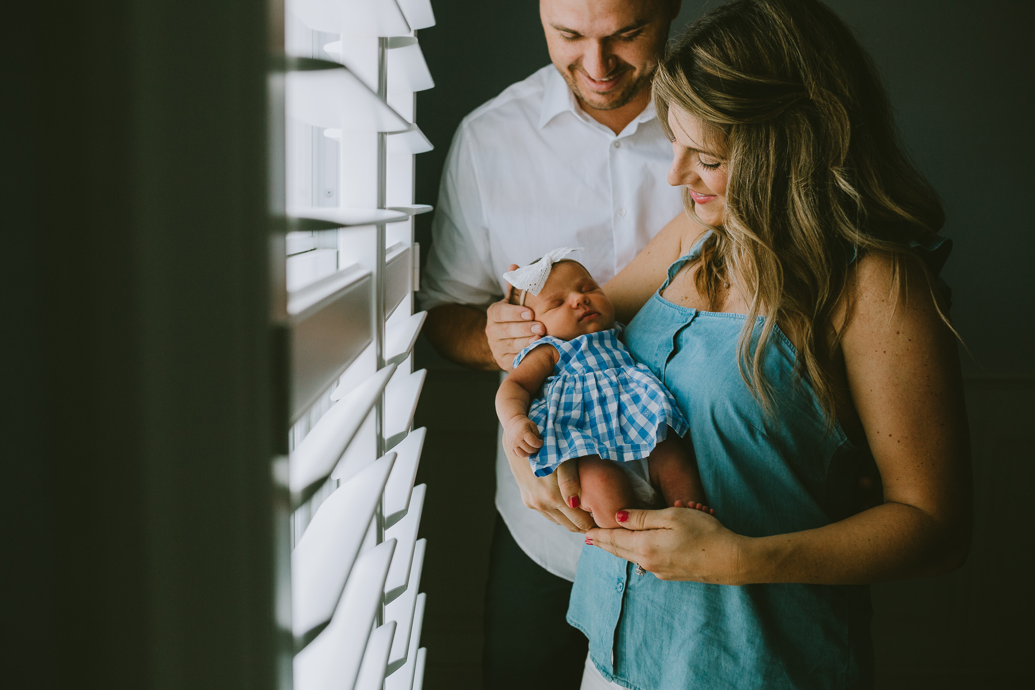 Parents holding newborn in natural light