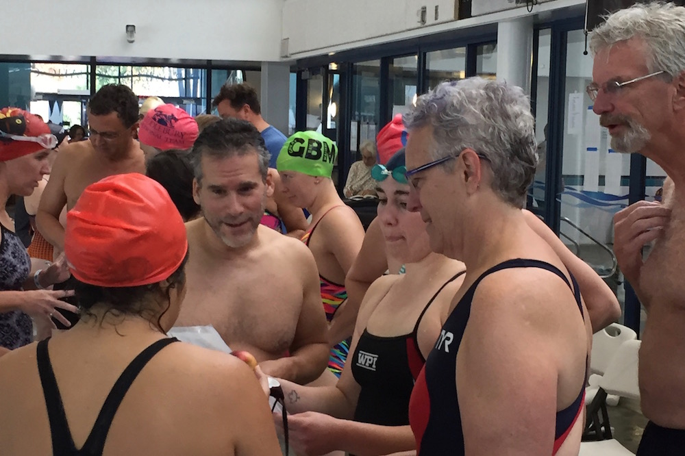 Swimmers review the different legs of the Icebreaker Relay and decide who does what.