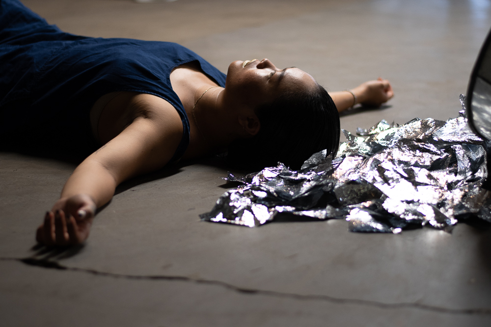 Belinda Adam laying on floor with head by silver paper, photo by Umi Akiyoshi.