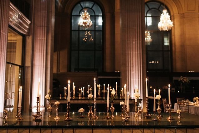 Nothing says romance like flickering candlelight. We flooded the entrance tables of this wedding reception with tapered candles, brass candlestick holders and single white roses, which created a warm and inviting ambiance. So simple, yet so beautiful! #weddinginspo 📸 @jennifervansonphoto