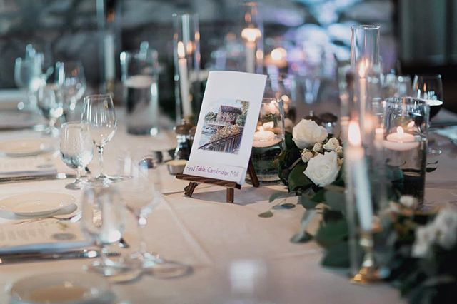 For this wedding, a king's table was set for the bridal party in front of a stone fireplace. Lush garland with delicate white roses were laid down the centre, surrounded by candles. The table was finished with personalized artwork of places the couple has travelled. 📸@boundlessweddings