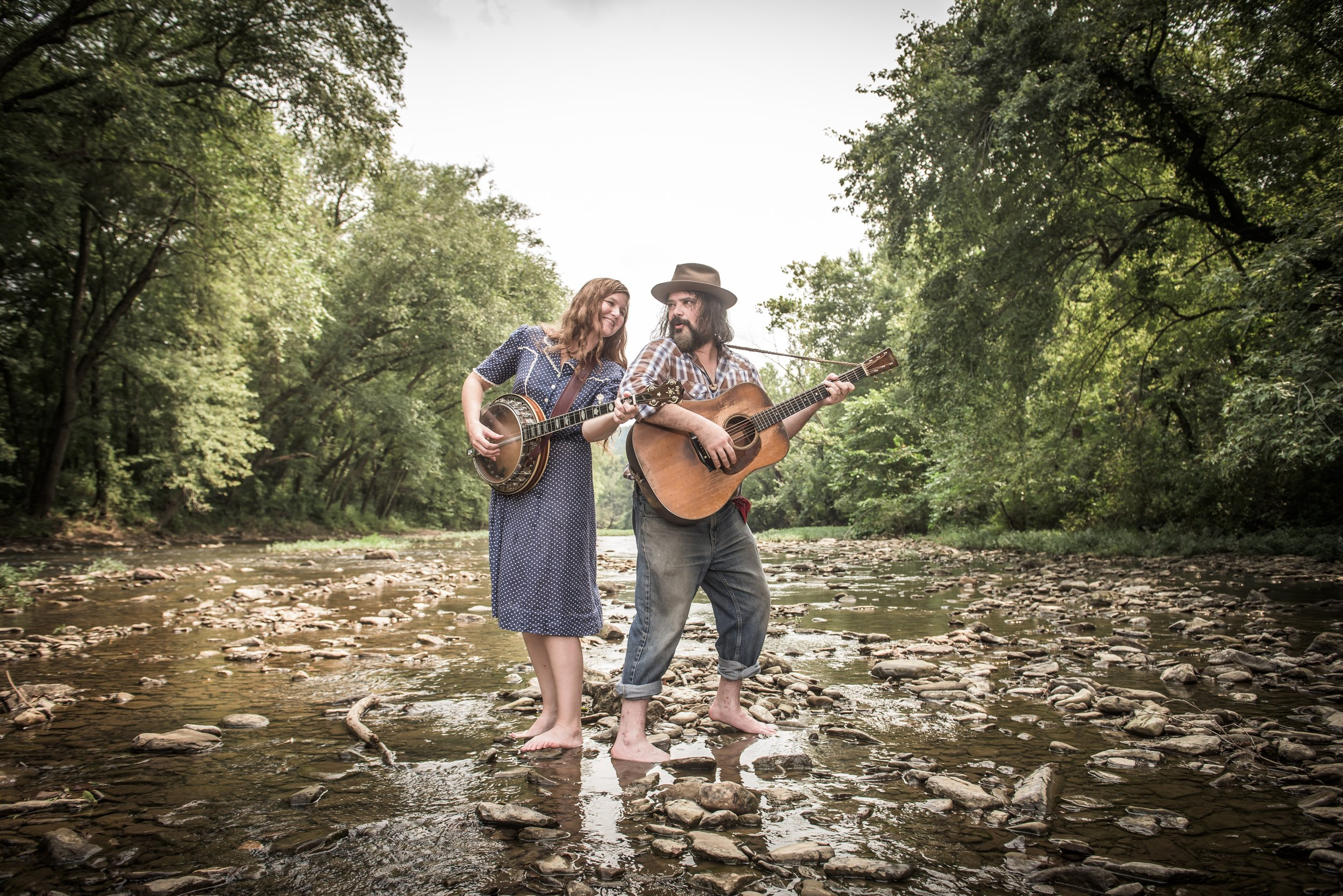 "The Creek Rocks - May 22nd & 29th, Every Wednesday evening in June.The Creek Rocks are a folk group from the Ozarks led by banjoist Cindy Woolf and guitarist Mark Bilyeu. These longtime musical collaborators worked together on Cindy's three CDs of original songs starting in 2005, they married in 2013, then established The Creek Rocks in 2015. Mark is a founding member of Ozarks family band Big Smith, with whom he toured and recorded for sixteen years. Their debut release, ""Wolf Hunter,"" is a collection of sixteen folk songs from the Ozarks, drawn from the collections of folklorists Max Hunter of Springfield, Missouri, Mark's hometown; and John Quincy Wolf of Batesville, Arkansas, where Cindy grew up. Joining them on the album are bassist Jason Chapman of the Chapmans bluegrass band and percussionist Jay Williamson, also of Big Smith, who currently serves as the band's go-to live percussionist. Cindy and Mark often perform as a duo, but are also buttressed by a host of musician friends when a full band seems decorous for the situation."