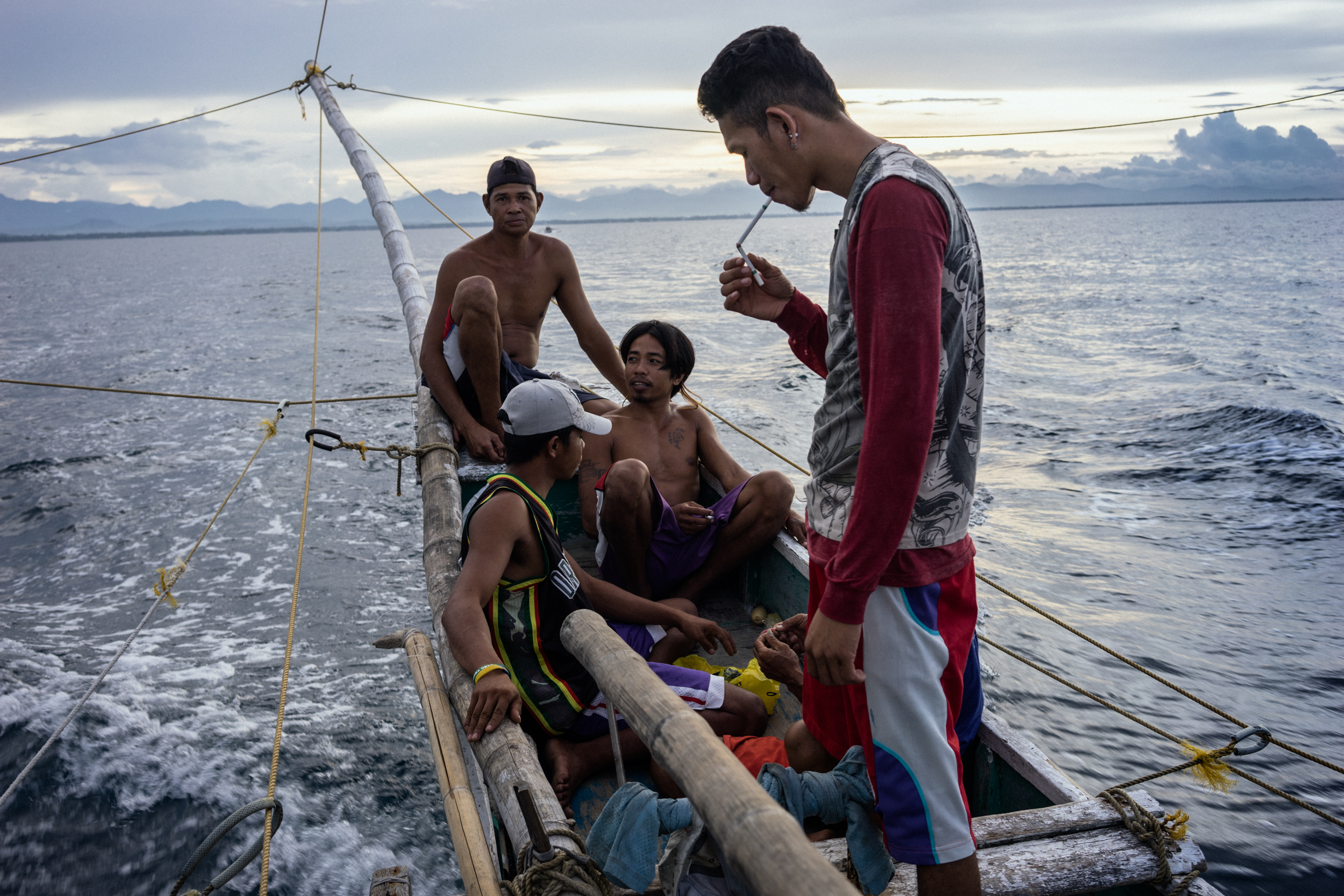 Kalibo, Philippines - September 21, 2015: The crew of a local fishing boat heads out for their night's catch. Members of the crew, who make approximately 35 USD per month, have expressed their desire to work on a larger fishing vessel for the promise of a higher income despite stories of fellow fishermen about the forms of abuse that happen on such vessels. / Hannah Reyes Morales