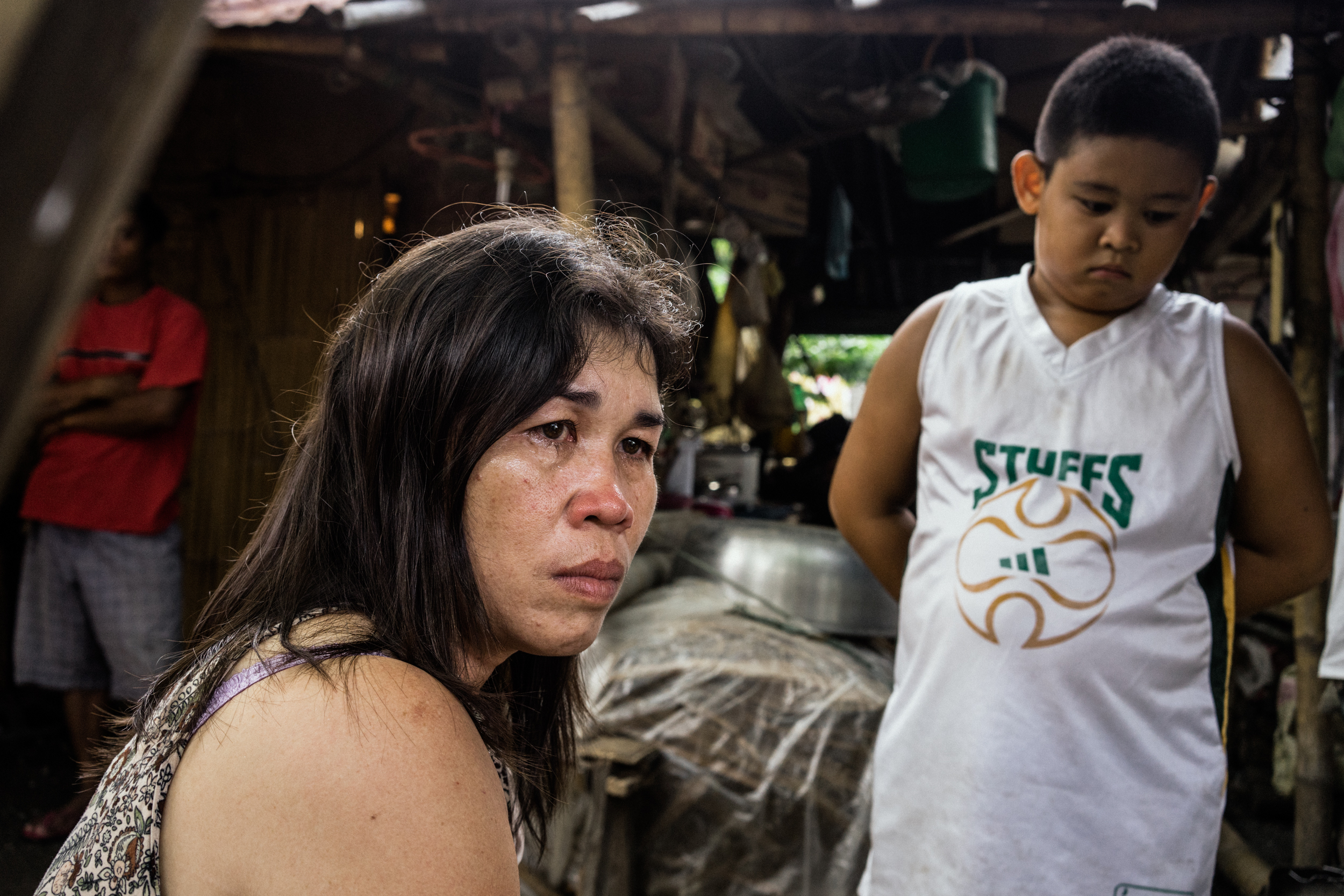 Kalibo, Philippines - September 20, 2015: Celia Robelo is seen with her son at a jail where she is being held on human trafficking and illegal recruitment charges following the death of a Filipino seafarer. Robelo claims that she did not have any knowledge of the illegal nature of her recruitment, claiming she only wanted to help these men find work and a way out of poverty. Hannah Reyes