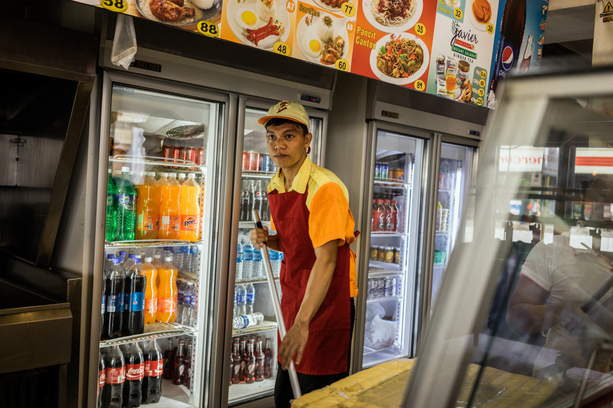 Kalibo, Philippines - September 20, 2015: Emmanuel Concepcion mops in the local fast food chain where he is currently employed after being repatriated from a fishing vessel. Emmanuel is a victim of a Singapore-based maritime manning agency that collected illegal placement fees from him, stationed him on a Taiwanese fishing vessel where he faced inhumane circumstances, and then failed to give him the salary he was promised. Hannah Reyes