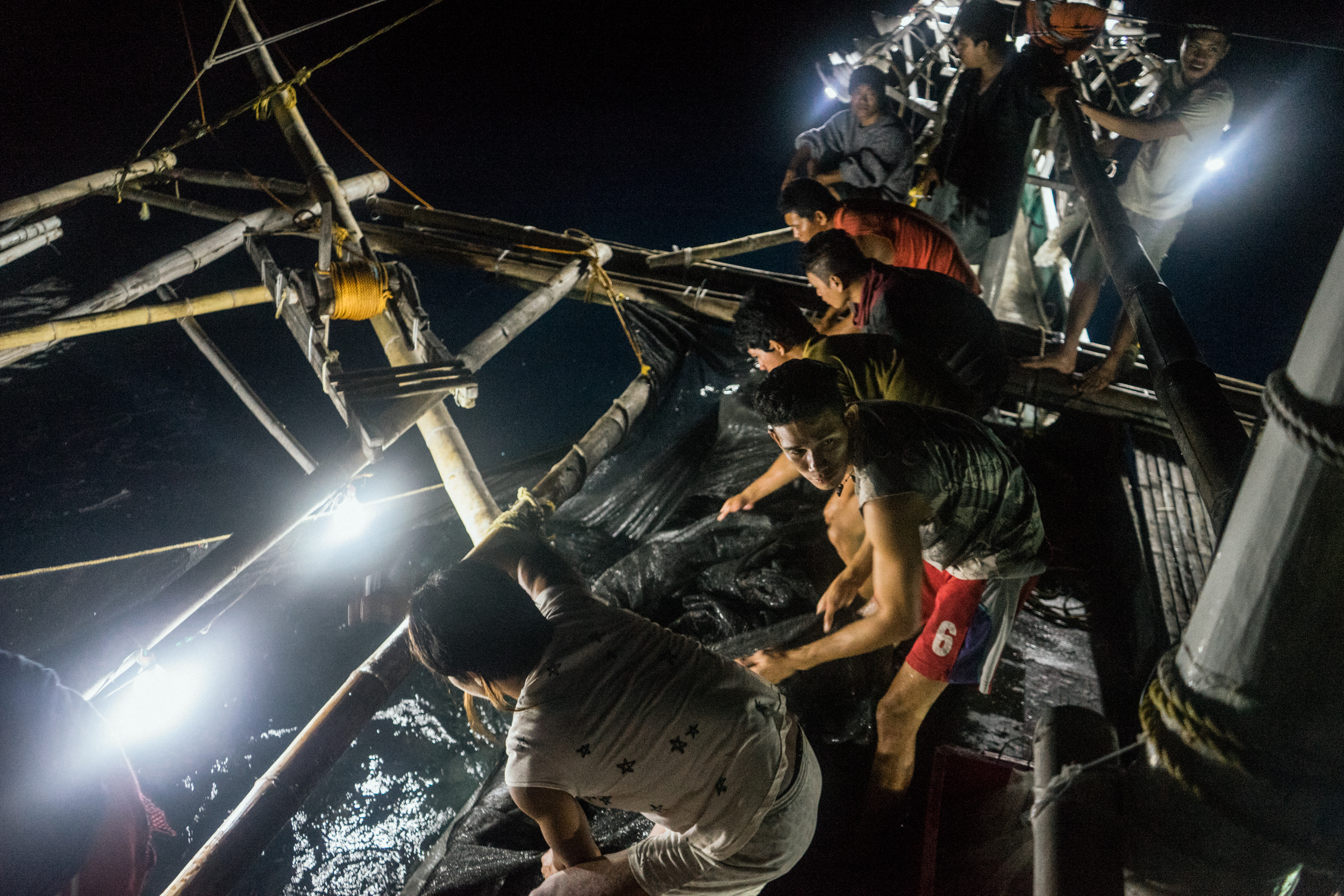 Kalibo, Philippines - September 21, 2015: Fishermen work in a local fishing boat. Members of the crew, who make approximately 35 USD per month, have expressed their desire to work on a larger fishing vessel for the promise of a higher income despite stories of fellow fishermen about the forms of abuse that happen on such vessels. Hannah Reyes