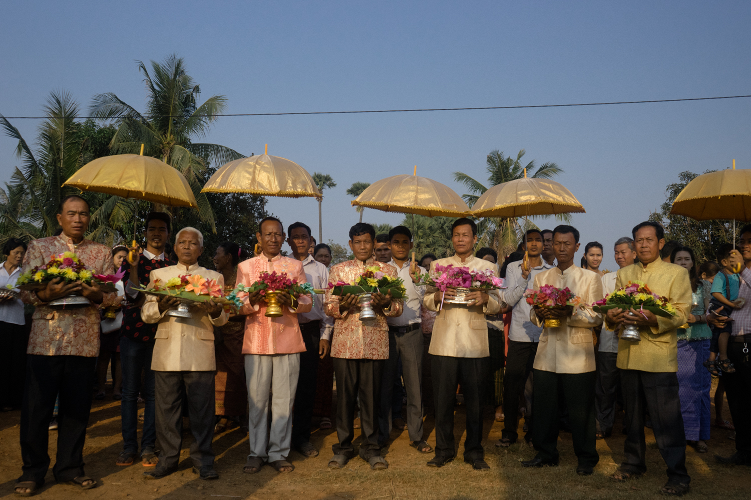 Grooms hold flowers during a fruit parade for a wedding ceremony held for victims of forced marriages by the Khmer Rouge. Several couples have decided to have a formal wedding ceremony almost four decades after their forced marriage, a crime which is today being tried as a crime against humanity by a war crimes tribunal.