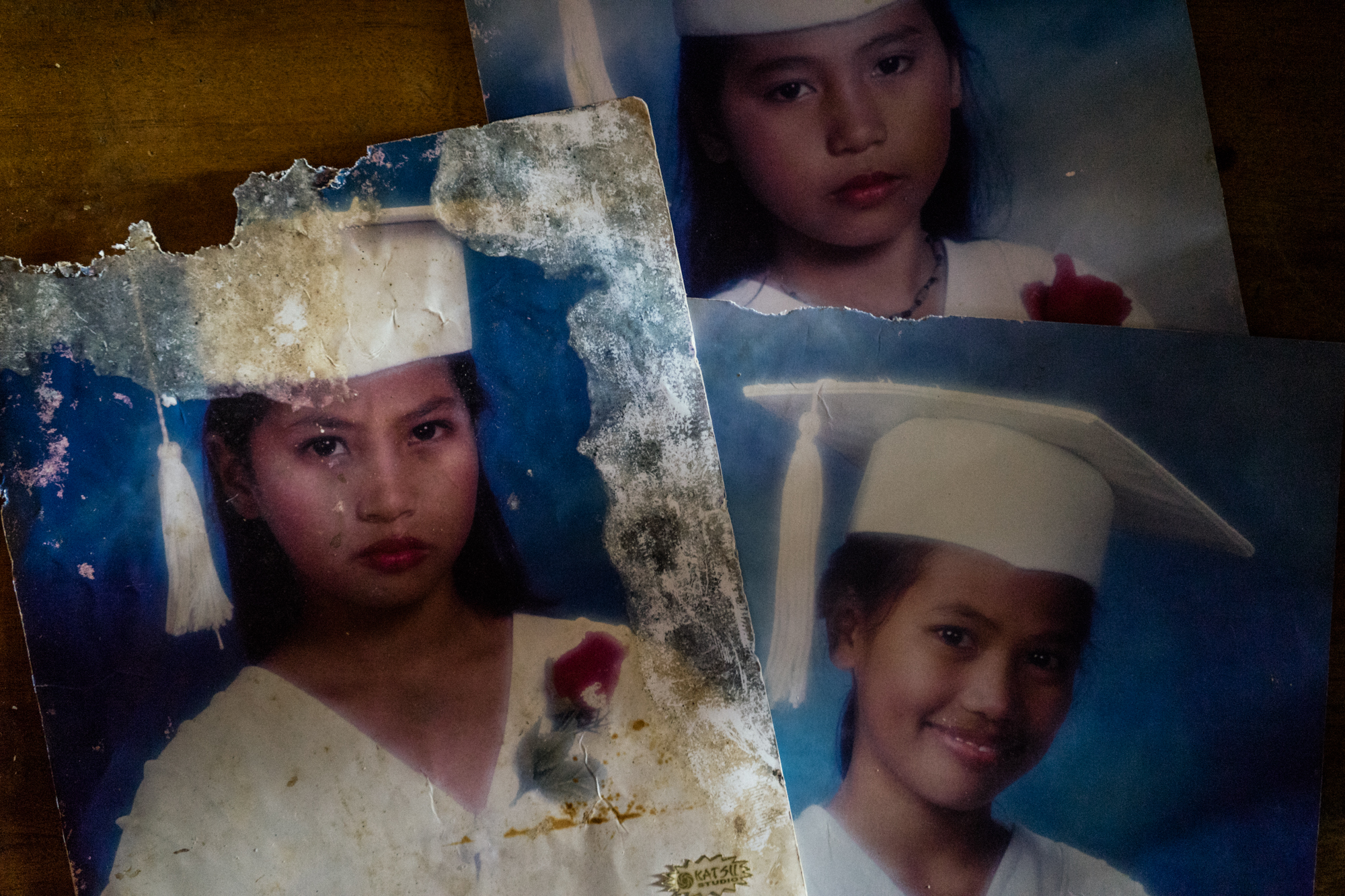 Salvaged water damaged graduation photos of Filipino sisters Jojo (left), Gemma (bottom right) and Joanne (top), in their home in the Visayas. Due to displacement from the frequency of storms, coupled with lack of work opportunities in their hometown, the sisters have all had to enter the sex trade in Angeles, known for its red light district.