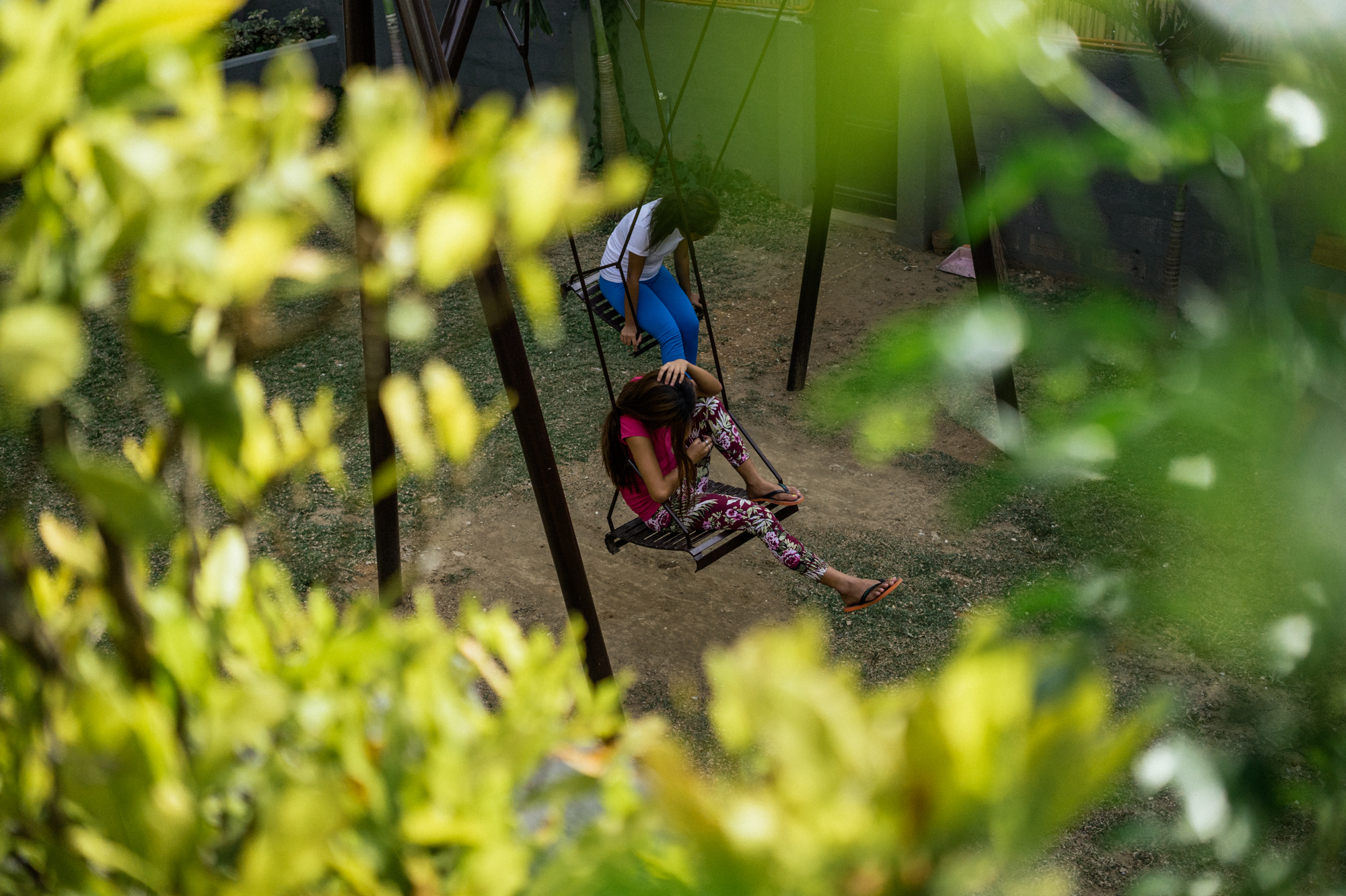 Young Filipina girls sit in the swings at a halfway house in Manila, where young girls who are rescued from the trade, stay until they can get legal employment.