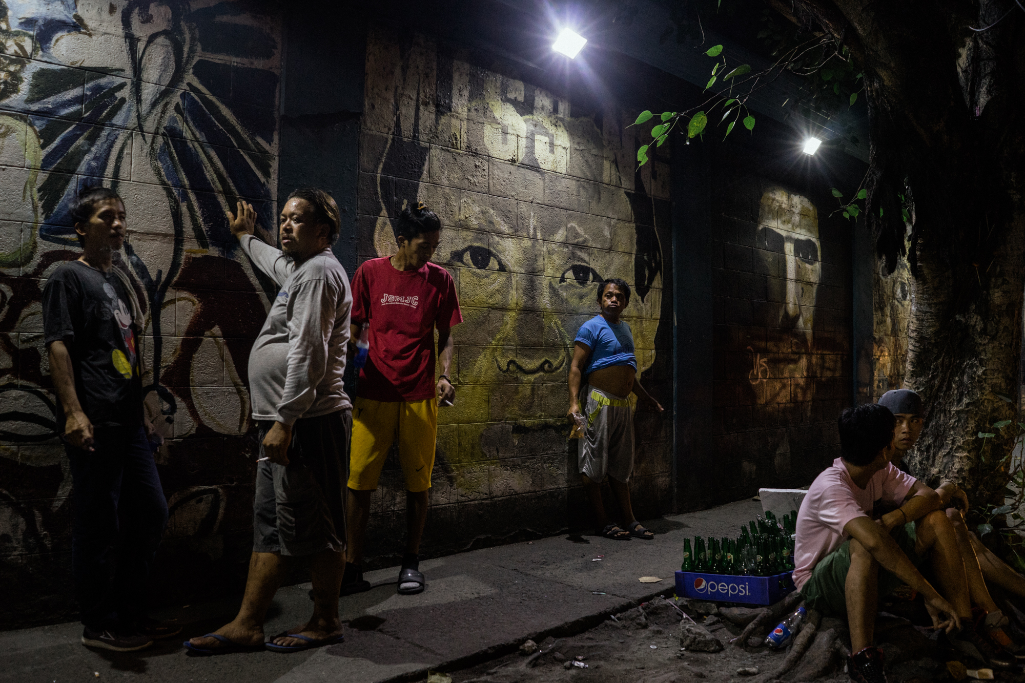 Filipino men are seen by a wall painting depicting President Rodrigo Duterte.