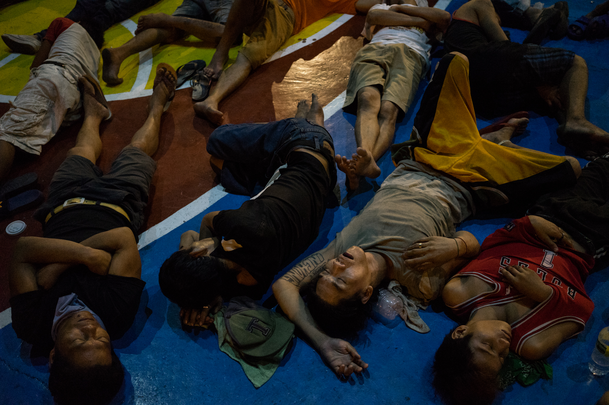 Filipino men are seen sleeping inside a basketball court in a prison on Saturday, September 17, 2016 in Quezon City, Philippines, after being rounded up for an investigation in conjunction with President Rodrigo Duterte's 'War on Drugs.'