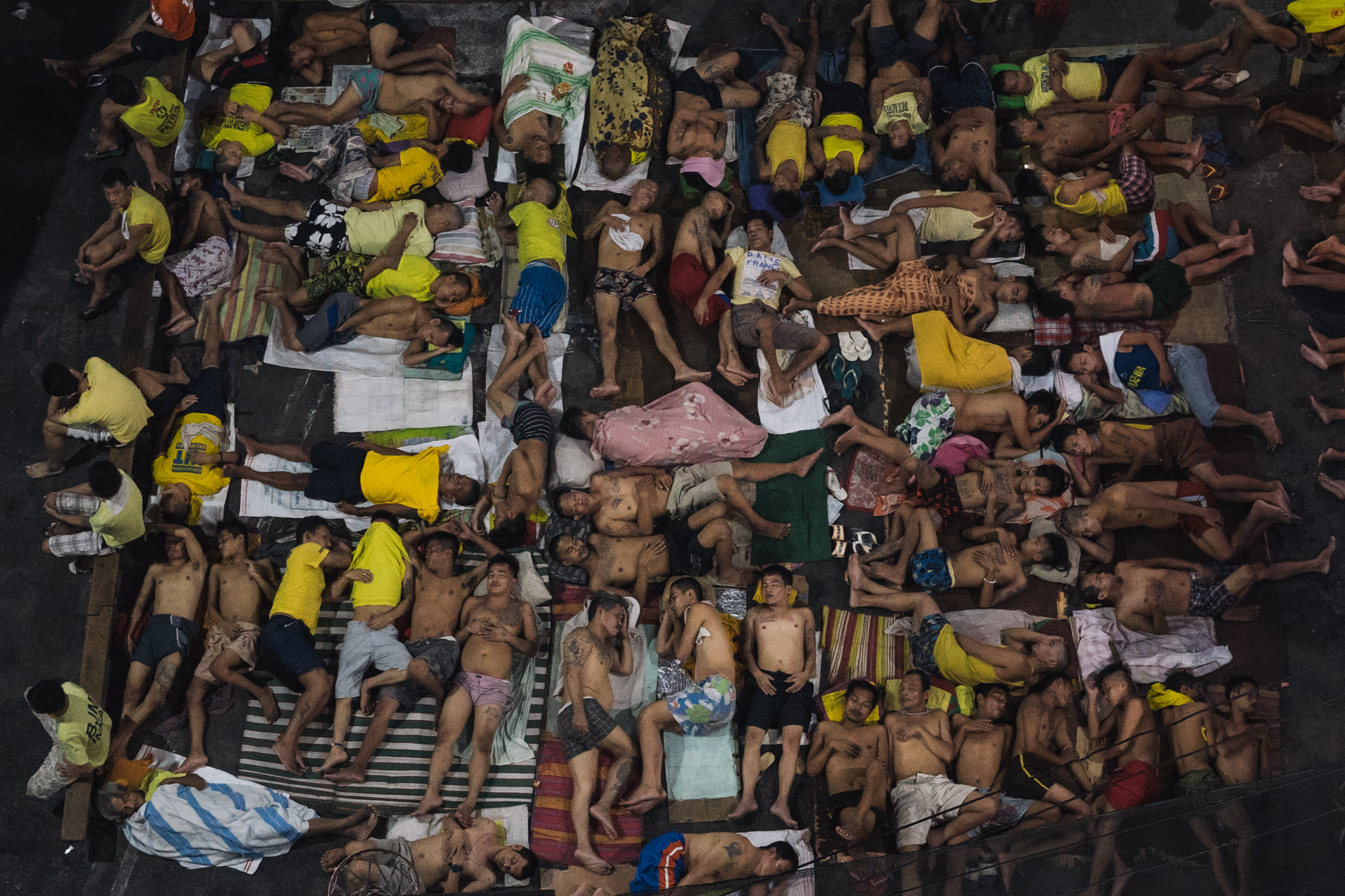 Men are seen sleeping inside a crowded jail on Wednesday, December 14, 2016 in Quezon City, Metro Manila, Philippines. As more men are arrested for drug use under Rodrigo Duterte's 'War on Drugs,' jails become congested, and friends and families of inmates report men refusing to walk free in fear of being killed by the police.