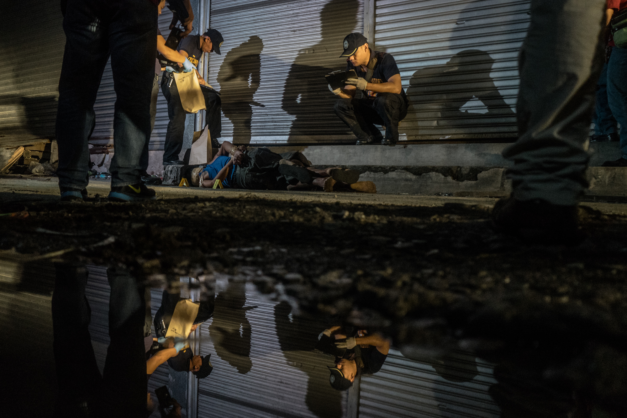 Police examine dead bodies on Thursday, November 17, 2016 in Metro Manila, Philippines. Philippine President Rodrigo Duterte has been widely criticized by international human rights organizations for his 'War on Drugs' which has taken thousands of lives since he took office, but his approval rating remains positive among the majority of Filipinos, especially the poor and the working class.