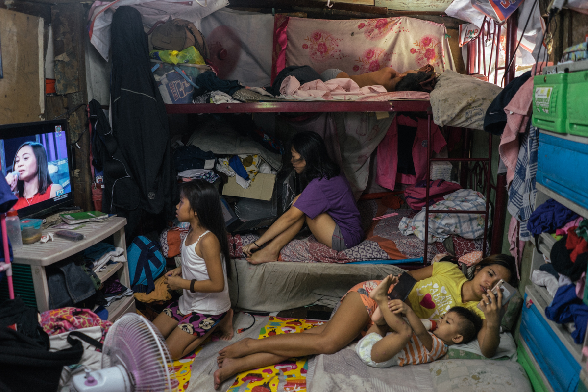 Inside the home of a family living in a shanty community in Manila. Families often rely on screen time to pass the time - prime time television often dominates life in these households, but today there is a rise of more affordable smartphones, with networks offering free facebook. / Hannah Reyes Morales Photography