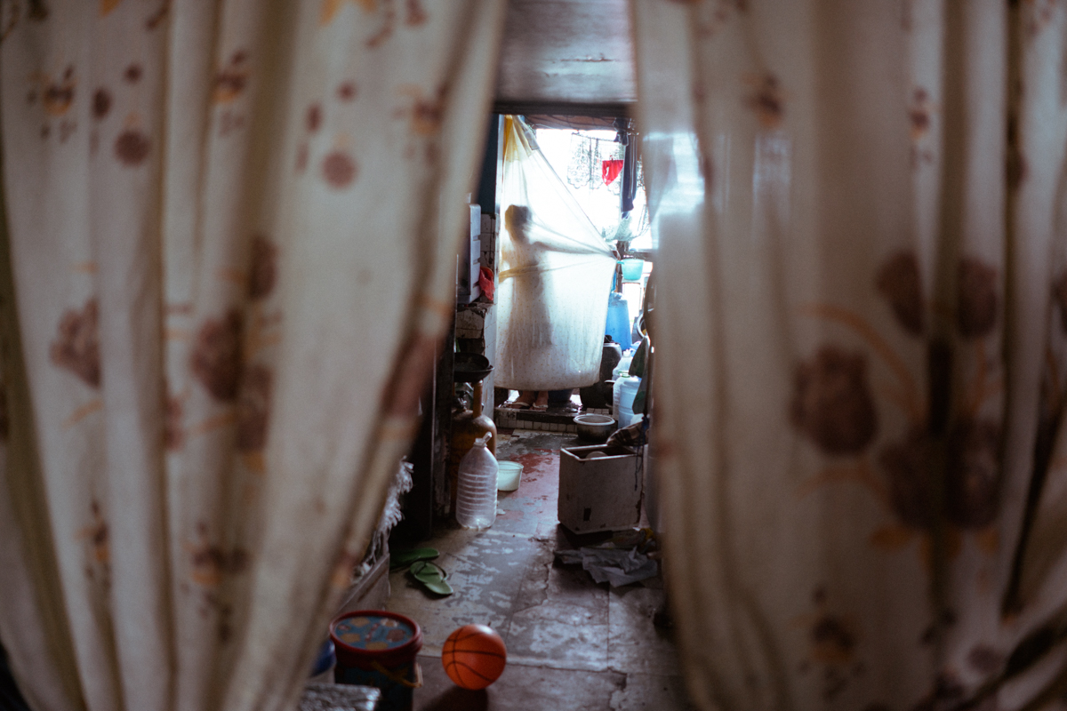 A Filipino boy hides from the camera in his tenement home in Metro Manila, Philippines.