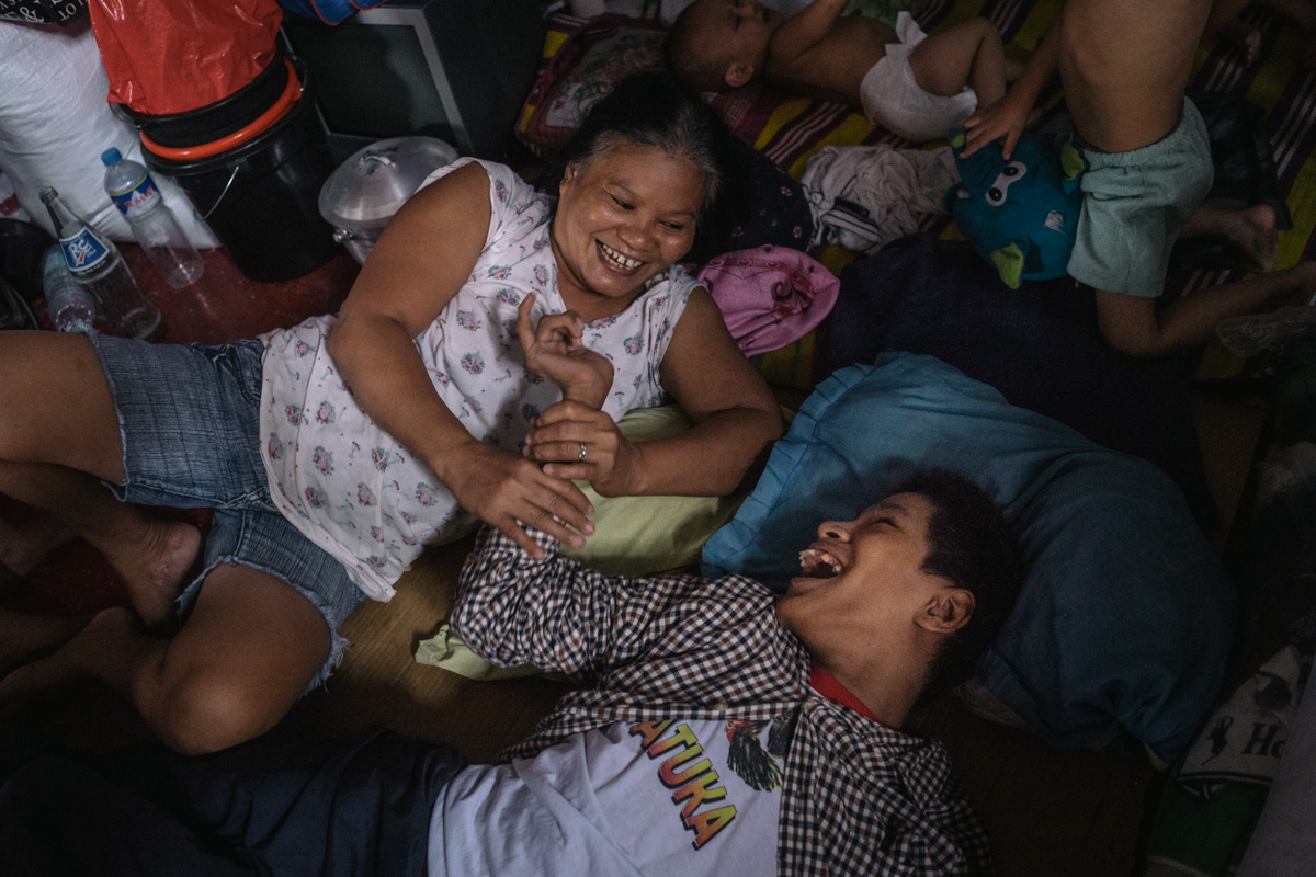 Jefferson and his caretaker are seen smiling at each other. For Jefferson, who is developmentally disabled, accessibility is limited in the shanty home where he lives.