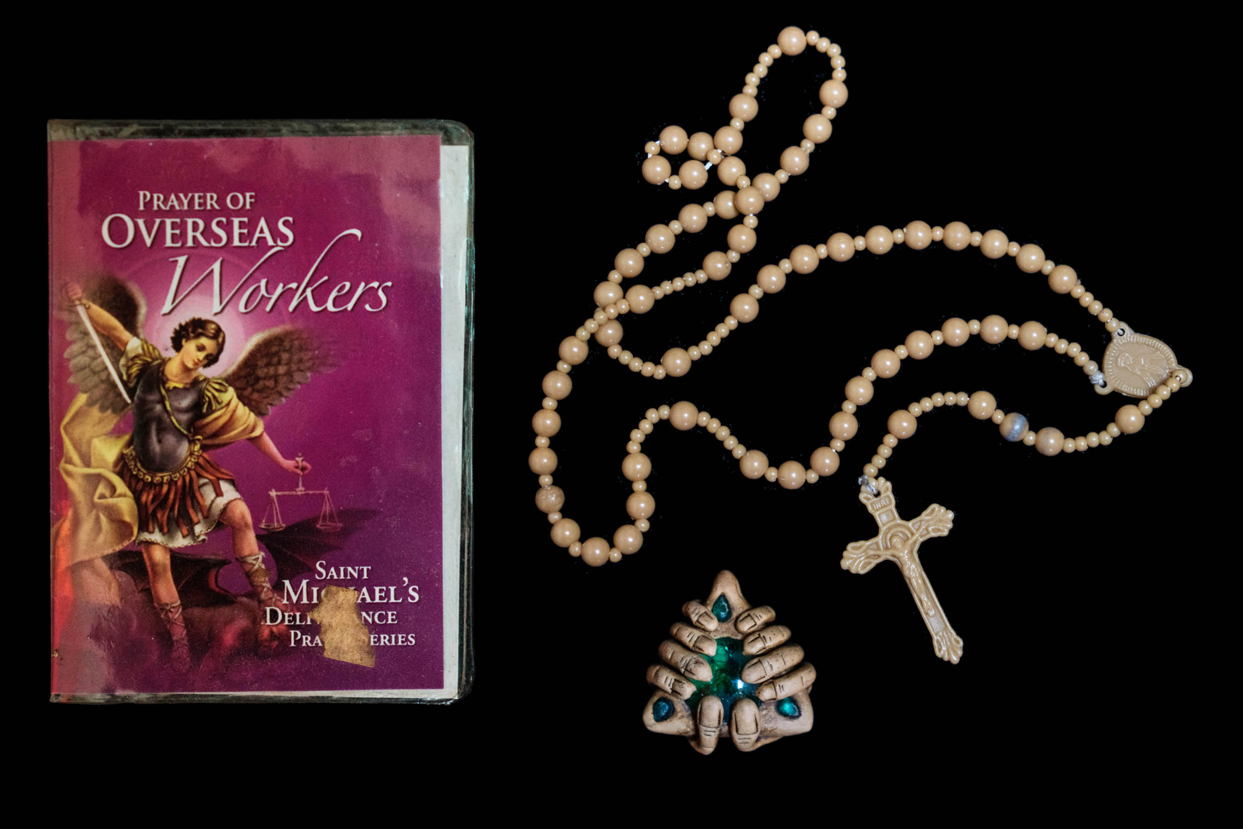Filipinos counteract the uncertainty of working overseas with artifacts of folk Catholicism: a rosary, an